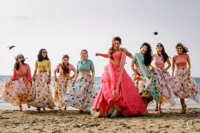 the bride and her bridesmaids at the beach during the mehendi ceremony