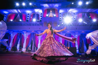 Purple lehenga embellished with floral resham and zari work styled with a pink dupatta and mustard choli by Shymmal and Bhumika