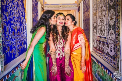 The bride posing with her mother and sister during her mehendi ceremony