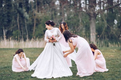 Bridesmaids helping the bride get ready for the wedding ceremony