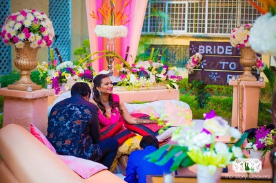 Outdoor mehndi ceremony set up in a theme of pink and peach with fresh flowers in gorgeous vases everywhere