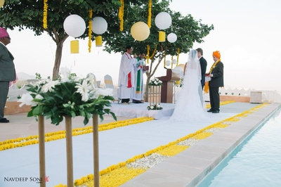 Wedding venue- Fategarh, Udaipur decorated in hues of white and yellow with globe lights, Marigold strings, petals and embellished strings