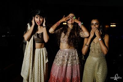 bride and bridesmaids posing quirkly at the sangeet ceremony