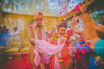 Showering the couple with rose petals as they take their Saat Pheras