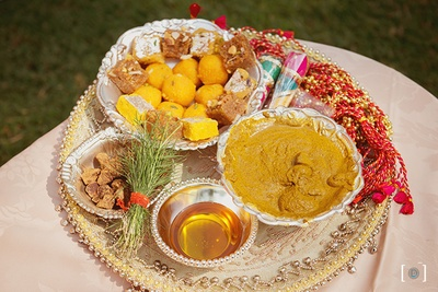 Beautifully decorated Haldi plate with haldi paste, oil and some sweets for the Haldi Ceremony .