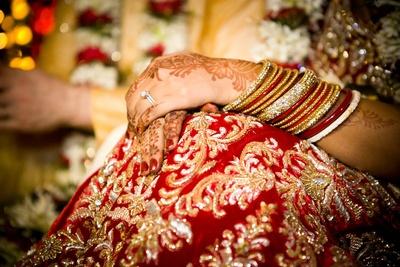 Red bridal lehenga embellished with gold zardozi work throughout