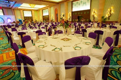 Table centerpieces, chair covered in white cloth and violet tie backs