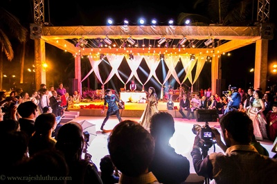 Open air sangeet ceremony with a stage setup with drapes and lights