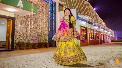 Yellow and pink sangeet lehenga featuring heavy paisleys embroidery, zari work and faux pearl tassels