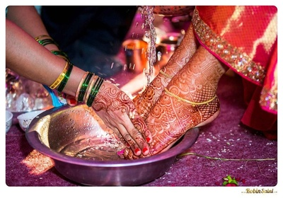 Feet covered in intricately patterned mehendi designs and styled with gold dainty paayal