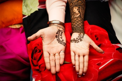 the bride and groom showing off their mehendi