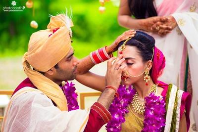Wedding sherwani styled with gold safa and feather topped Kalgi