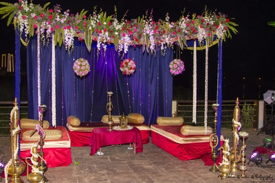 Outdoor setting with golden bolsters, floral ceiling and hookas