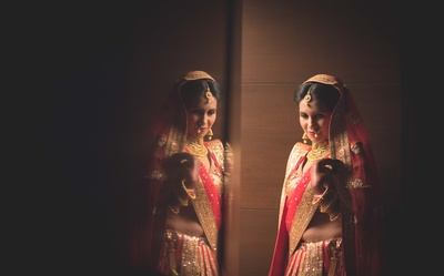 Decked in a bright red wedding lehenga embellished with sequined motifs, gold laces and thread work