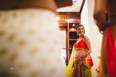 Decked up in beautiful orange and green lehenga styled with minimal jewellery for the sangeet ceremony.