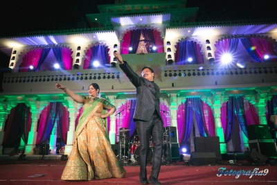 Parents of the groom dressed in lehenga and suit for pink and blue themed sangeet ceremony