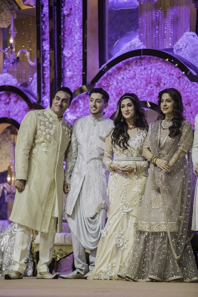 the bride and groom posing for a photo with Juhi Chawla at the reception