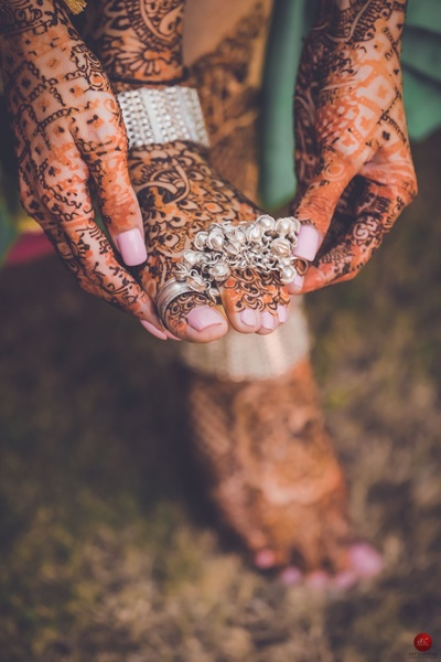Close up of the bride's unique foot mehendi design paired with traditional silver  toe rings