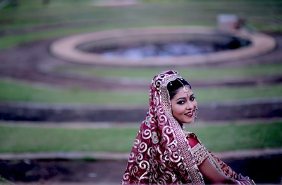 Bride wearing a red and gold shimmery dupatta with delicate bridal jewellery including an oversized nath and dainty maangtikka