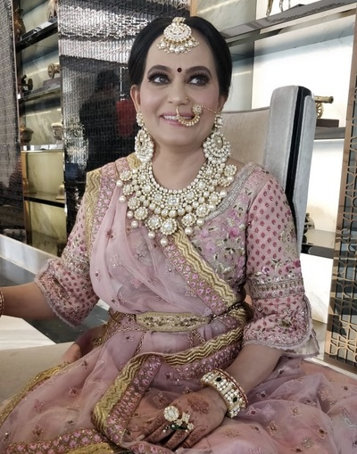 The bride's mother in a blush pink lehenga and heavy jewellry