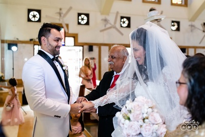a beautiful shot of the bride and the groom meeting at the altar