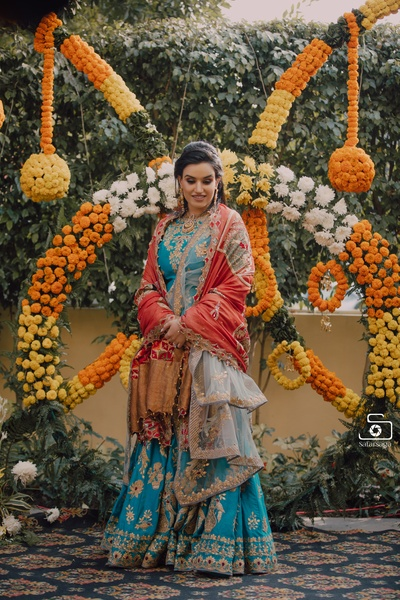 The bride is looking absolutely stunning in this bright blue lehenga with gold embellishments!