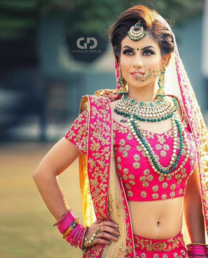 11. A bright pink lehenga combined with some gold and emerald jewellery