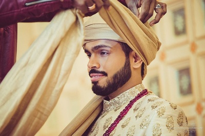 Groom getting ready in a Sabyasachi suit  for the wedding day