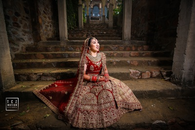 the bride in a heavily detailed red lehenga for the hindu ceremony