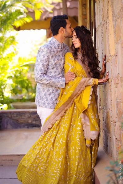 Bride and groom posing romantically at their mehendi\