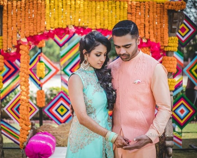Bride and groom pose together while the bride shows off her mehndi