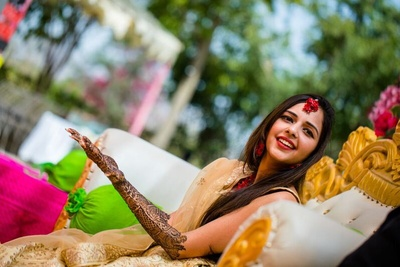 a candid capture of the bride at her mehendi ceremony