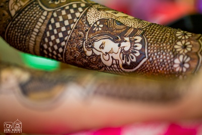 Hands covered in intricately patterned mehendi design