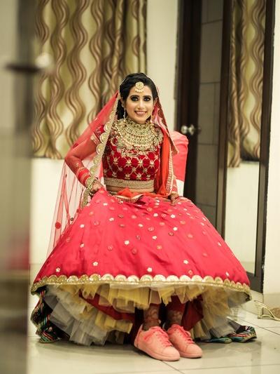 the bride in pink sneakers under her red lehenga