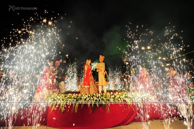 Open air varmala ceremony with an elevated flower decorated stage at the Cube, Mumbai