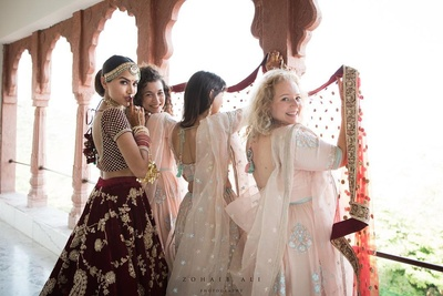 bride in a fun click with bridesmaids in her wedding lehenga