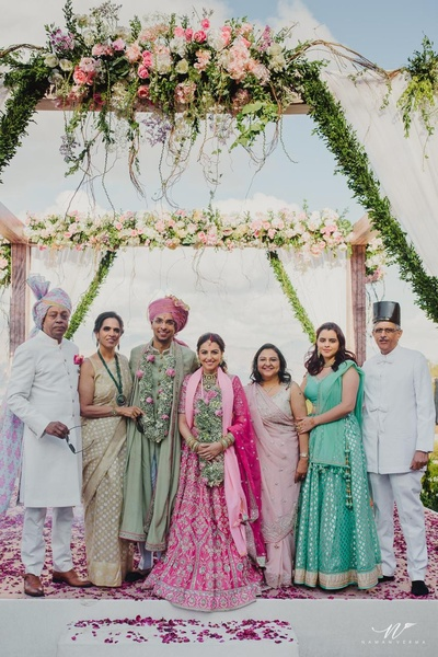 The bride and groom with their family on their wedding day'