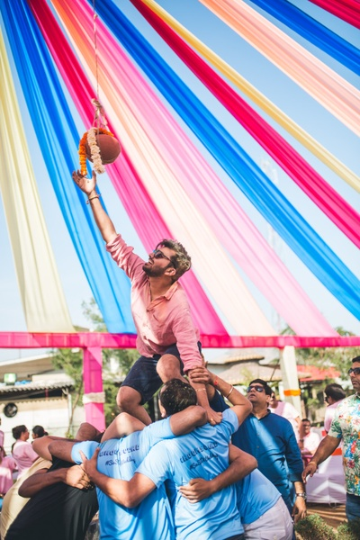 the groom having fun at the dahi handi event at their mehendi cermony