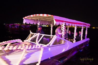 Bride and groom entering the vedi mandap, in a boat decorated with white Marigold strings