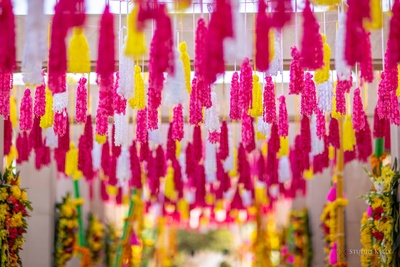A roof filled with suspended colourful tassels for the mehendi ceremony.