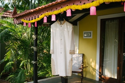 The groom's ivory kurta with delicate golden embroidery
