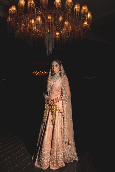 The bride in a pastel peach lehenga for her wedding