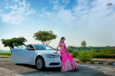 The bride looks stunning while striking a pose, lebaing against her car.