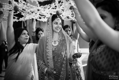 Bride being escorted under a phoolon ki chaadar