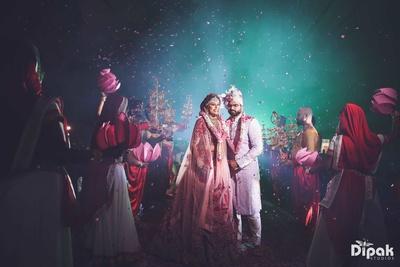 Bride and groom pose for Dipak Studios post the varmala exchange