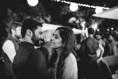 Black and white photography of bride and groom at the sangeet function