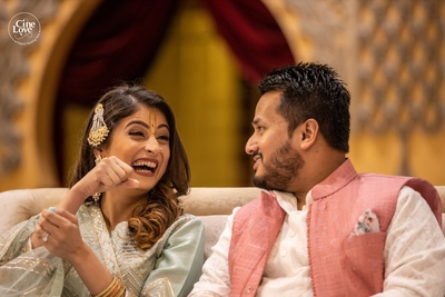 The bride and groom share a light moment at the Bhajan Sandhya.