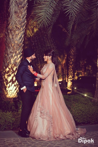 Bride and groom dance together during their reception in Amanta Lawns, Delhi
