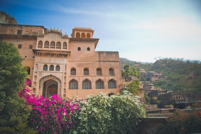 Ancient wings of Neemrana Fort palace with lush green trees adorned with beautiful flowers