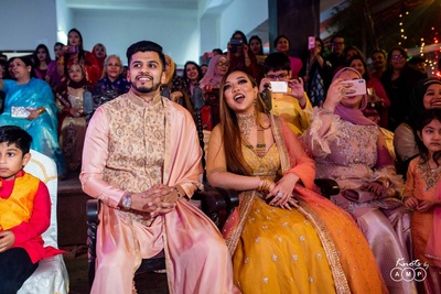 The couple enjoying dance perfromances by friends and family at the sangeet ceremony.